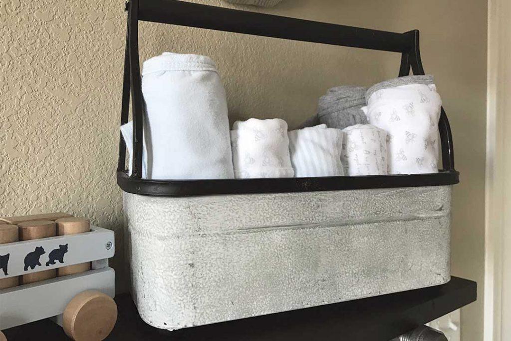 metal tool bin with burp cloths and blankets on top of DIY industrial pipe shelf in nursery