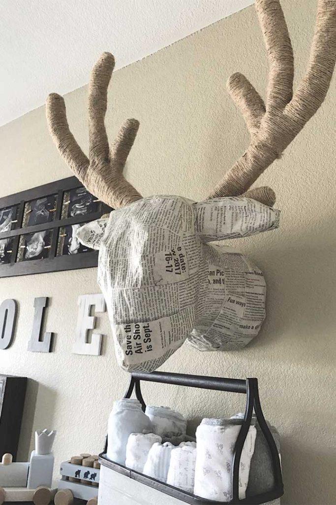 DIY paper mache deer head on collage wall in woodland nursery