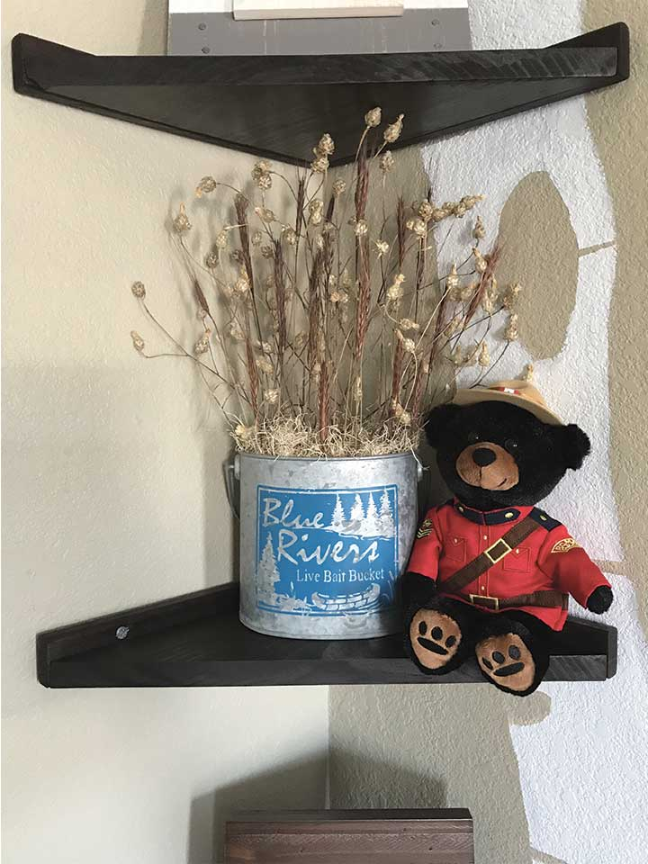 DIY wood corner shelves with a Canadian Mountie bear and galvanized metal pail fill with dried floral.
