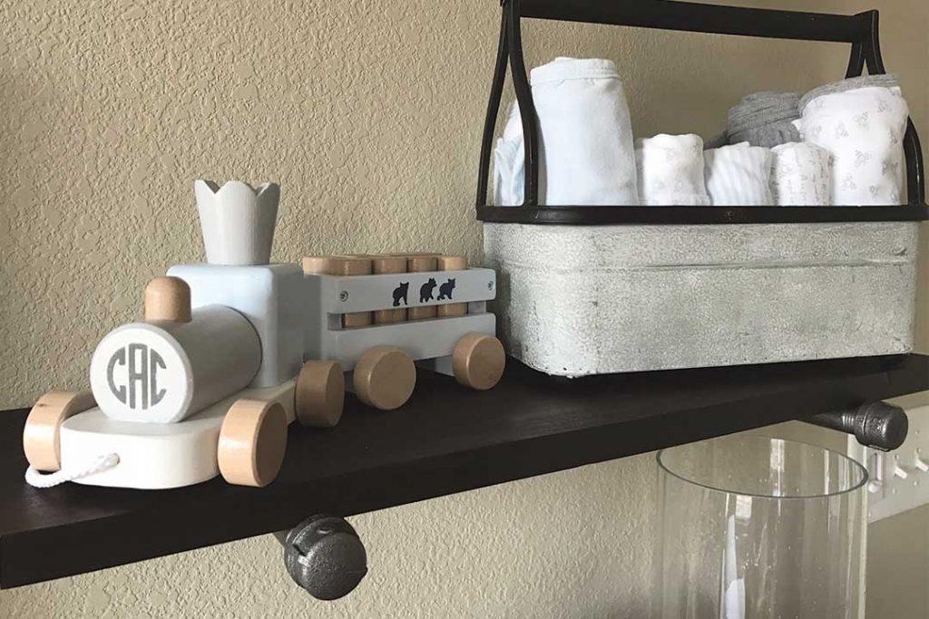 DIY industrial pipe shelf on nursery wall