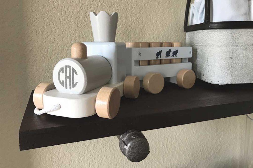 wood train on top of DIY industrial pipe shelf in nursery