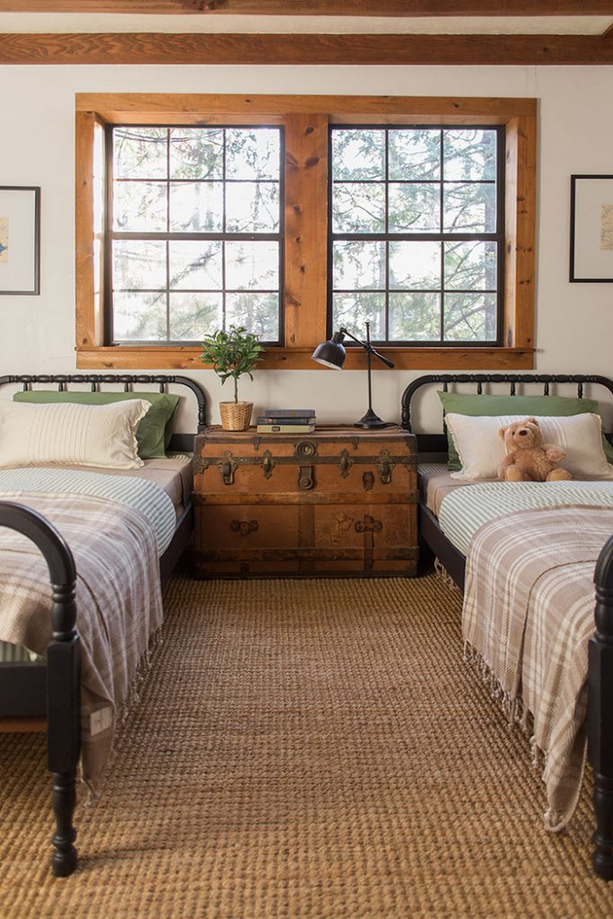beautiful neutral children's room with antique steamer trunk, two Jenny Lind beds painted black, and natural wood window trim